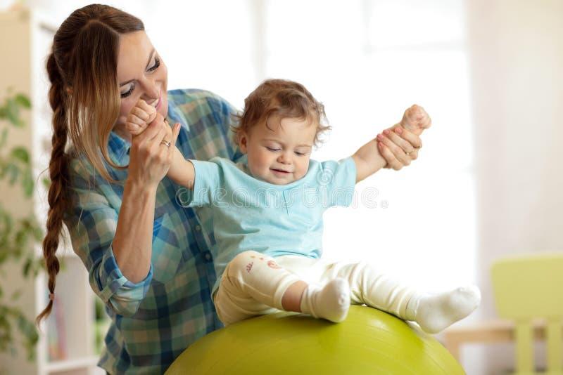 Mãe e bebê felizes na bola da aptidão no berçário em casa Gimnastics para crianças no fitball fotos de stock