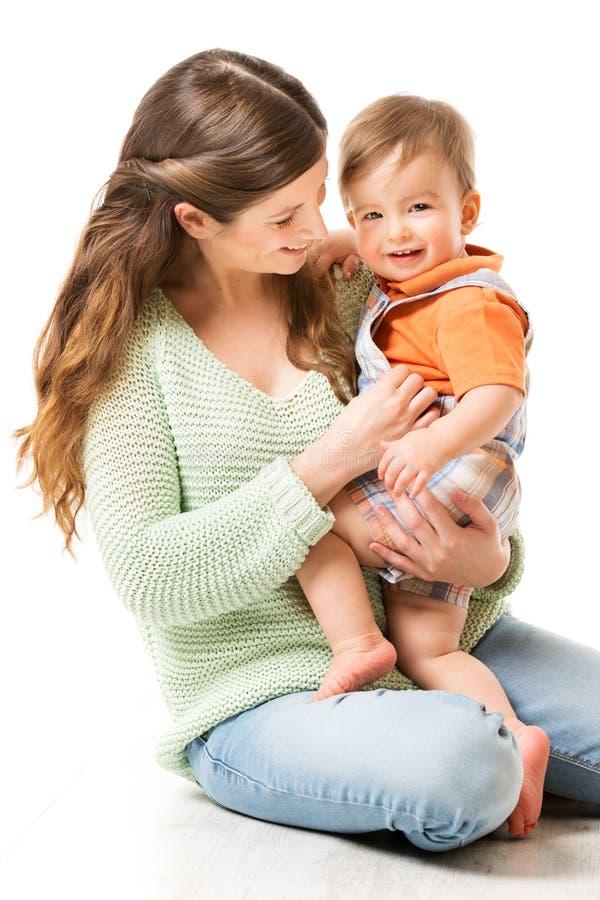 Mãe e bebê, mamã feliz com a criança de um ano da criança que senta-se no assoalho, família no branco imagens de stock royalty free
