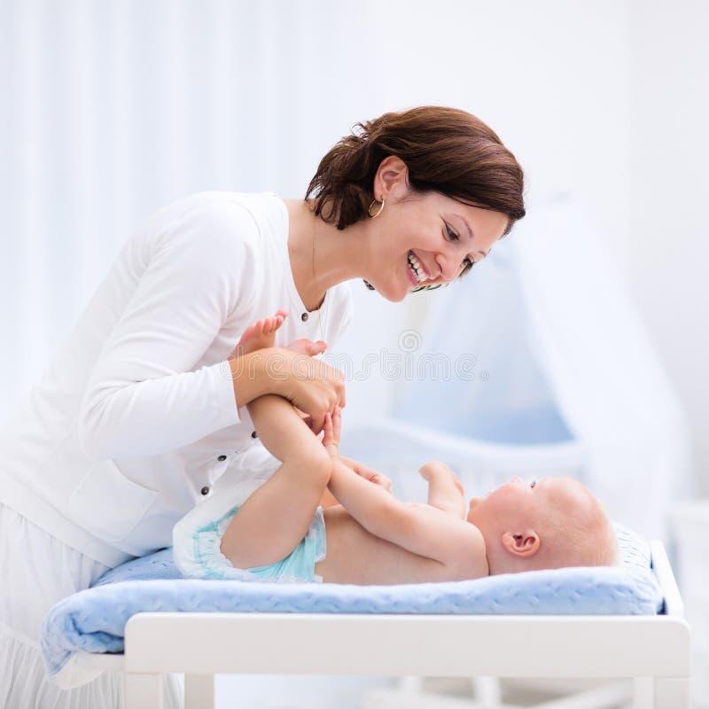 Mãe e bebê na tabela em mudança imagens de stock royalty free