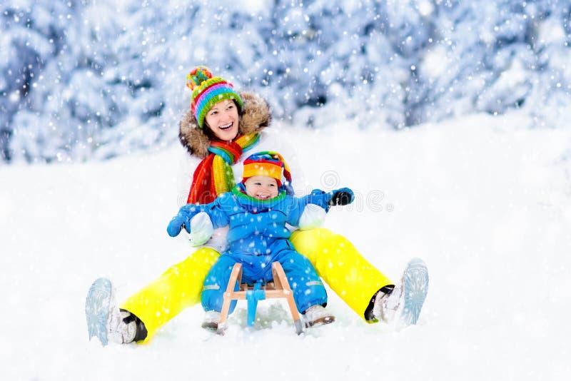 Mãe e bebê no passeio do trenó Divertimento da neve do inverno fotos de stock royalty free