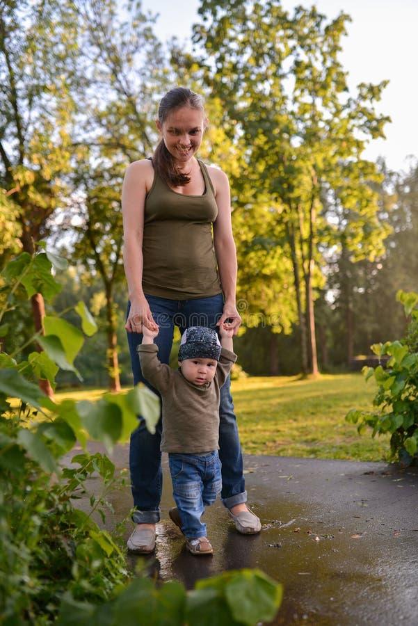 Mãe e bebê que andam no parque Primeiras etapas do rapaz pequeno engraçado foto de stock