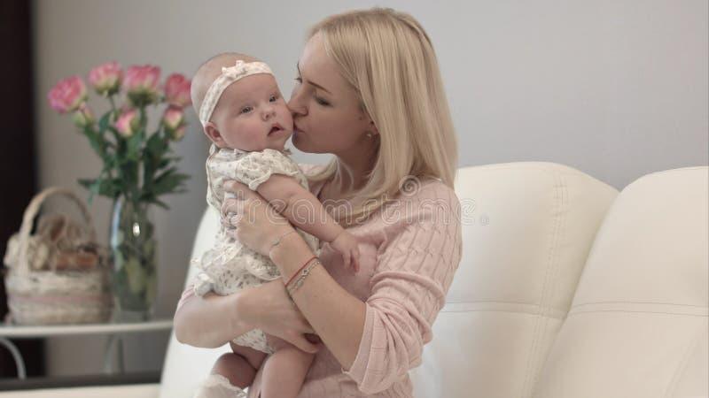 Mãe e bebê que beijam e que abraçam Família feliz imagem de stock