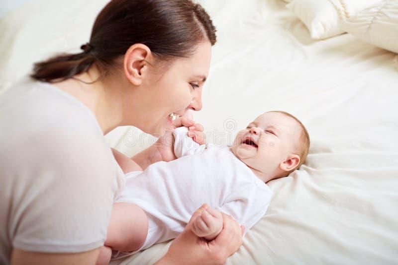 Mãe e bebê que jogam e que riem Uma família feliz imagem de stock