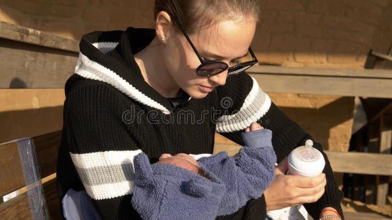 Mãe e bebê que preparam-se para a fórmula de alimentação que senta-se no banco fotos de stock royalty free