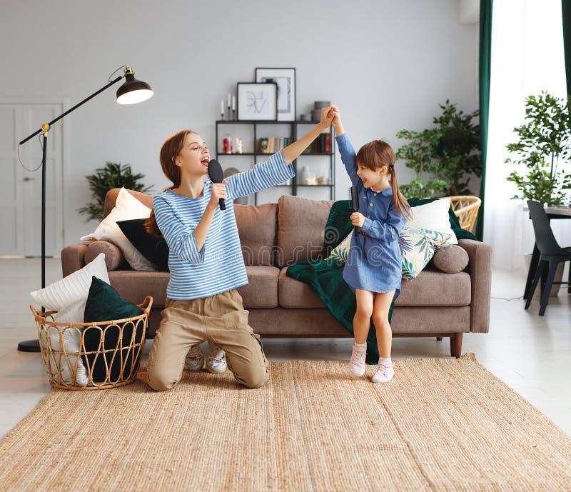 Mãe e brincadeira felizes da família em casa e para cantar com pentes foto de stock royalty free