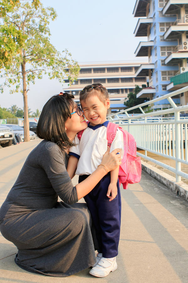 A mãe e a criança adorável com escola backpack na frente do kinderg foto de stock royalty free
