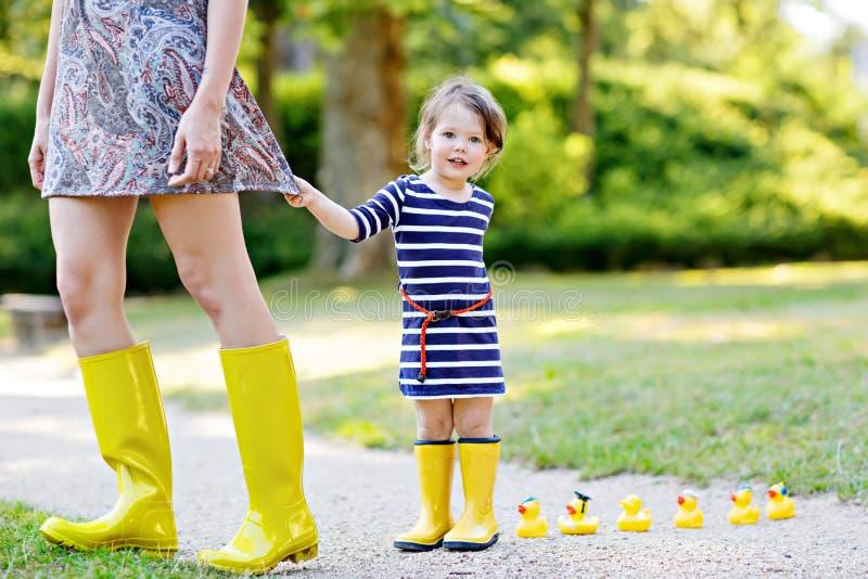Mãe e criança adorável pequena em botas de borracha amarelas, olhar da criança da família, no parque do verão Mulher e bonito bon foto de stock
