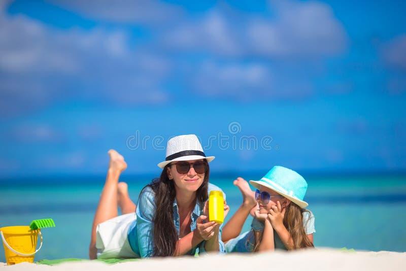 Mãe e criança com loção para bronzear em tropical imagem de stock royalty free
