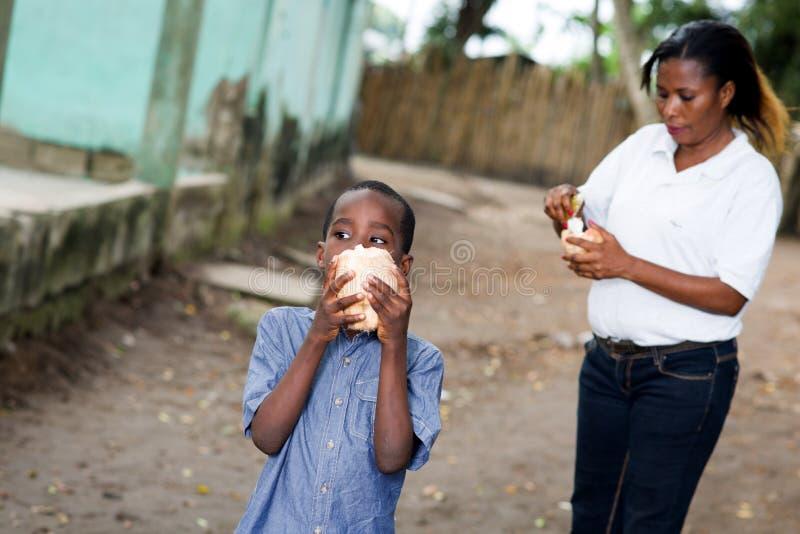 A mãe e a criança comem um coco imagens de stock