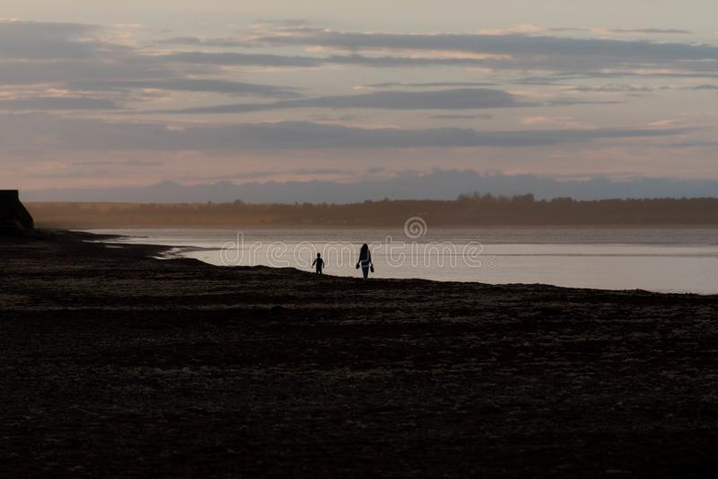 Mãe e criança como silhuetas na exploração e no unkn do por do sol imagem de stock