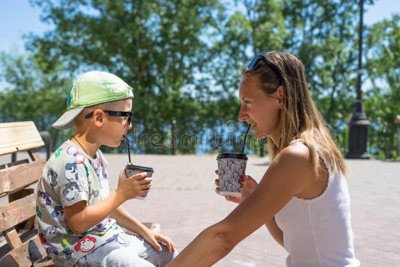 Mãe e criança de sorriso felizes - menino - apreciando o tempo da refeição no café da rua, restaurante, tempo da família, almoço  imagem de stock