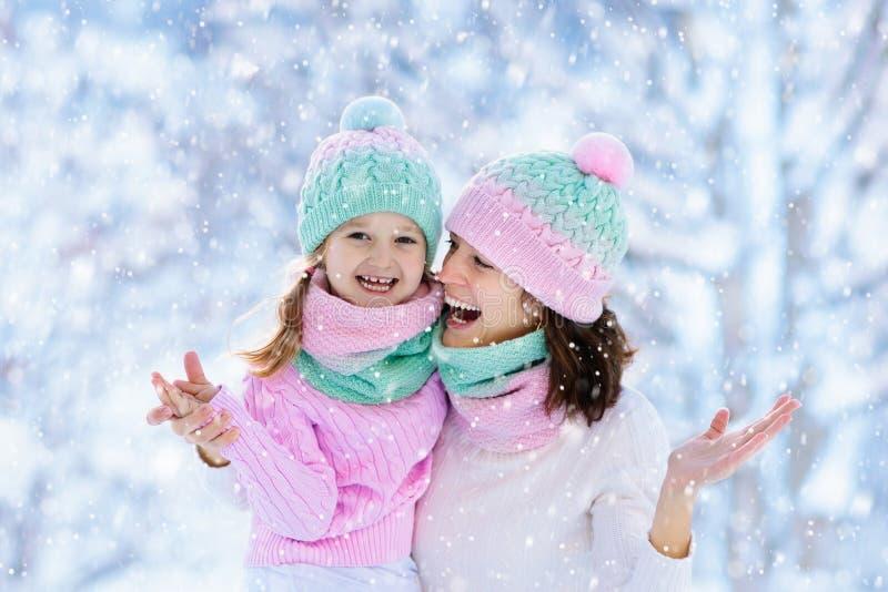Mãe e criança em chapéus feitos malha do inverno na neve foto de stock royalty free
