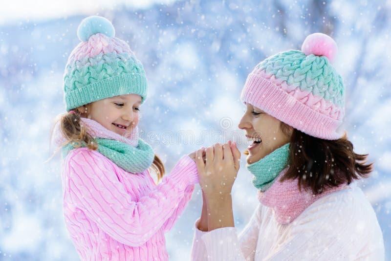 Mãe e criança em chapéus feitos malha do inverno na neve fotografia de stock