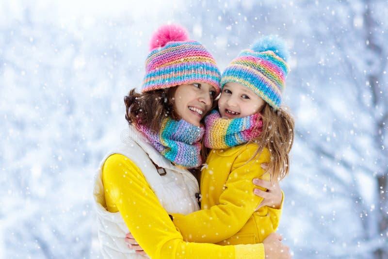 Mãe e criança em chapéus feitos malha do inverno na neve fotos de stock