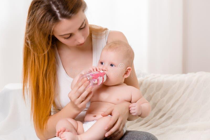 Mãe e criança em uma cama branca Mamã e bebê no tecido que joga no quarto ensolarado fotografia de stock royalty free