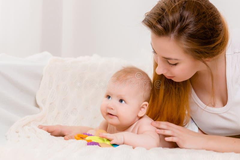 Mãe e criança em uma cama branca Mamã e bebê no tecido que joga no quarto ensolarado fotos de stock royalty free