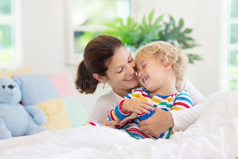 Mãe e criança na cama Mamã e bebê em casa imagem de stock