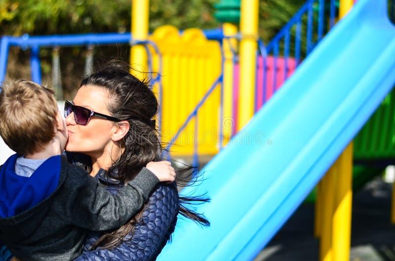 Mãe e criança no campo de jogos foto de stock