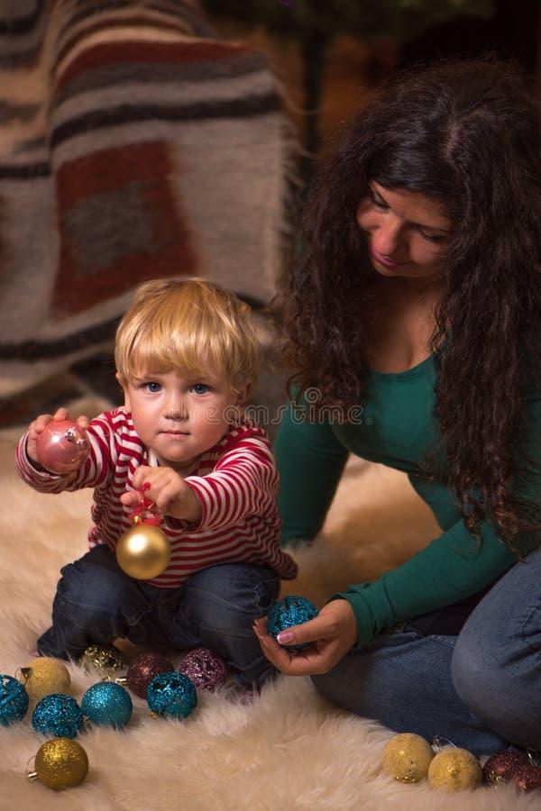 A mãe e a criança pequena que jogam com árvore dos christmass borbulham fotos de stock royalty free