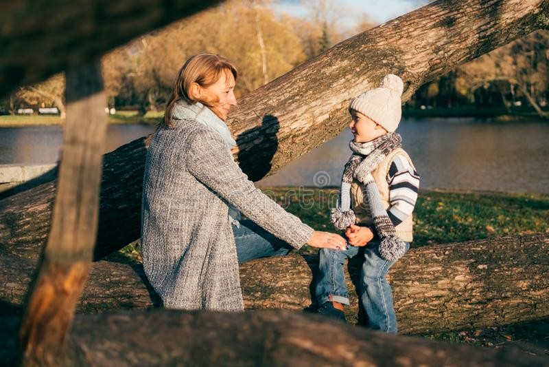 Mãe e criança que abraçam no parque do outono perto do lago fotos de stock