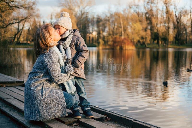 Mãe e criança que abraçam no parque do outono perto do lago Filho feliz com a mamã que tem o divertimento, relaxamento, apreciand fotografia de stock royalty free