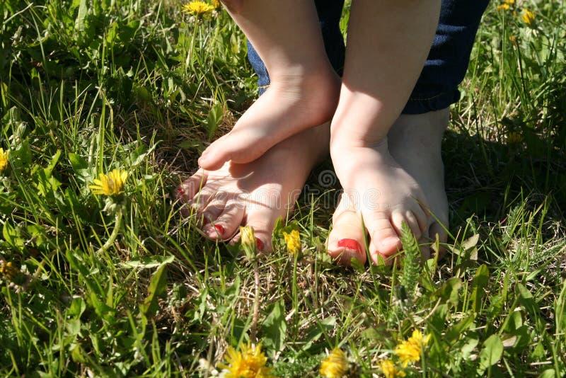 Mãe e criança que andam com os pés descalços na grama imagens de stock royalty free