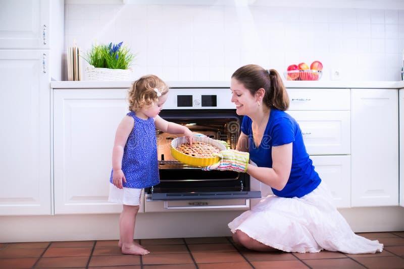 Mãe e criança que cozem um bolo imagem de stock royalty free