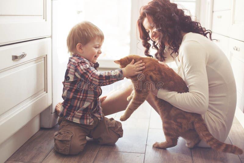 Mãe e criança que jogam com gato