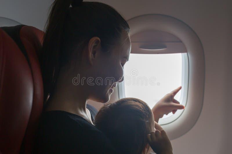 Mãe e criança que olham para fora a janela de um avião Viagem com crianças Férias de família fotos de stock royalty free