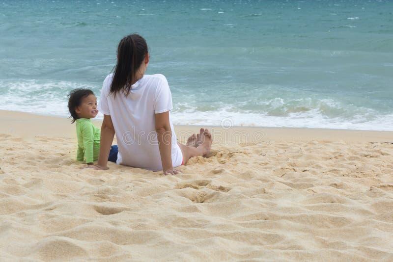 Mãe e criança que sentam-se na praia que tem o divertimento fotos de stock royalty free