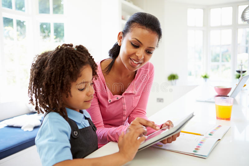 Mãe e criança que usa a tabuleta de Digitas para trabalhos de casa fotografia de stock