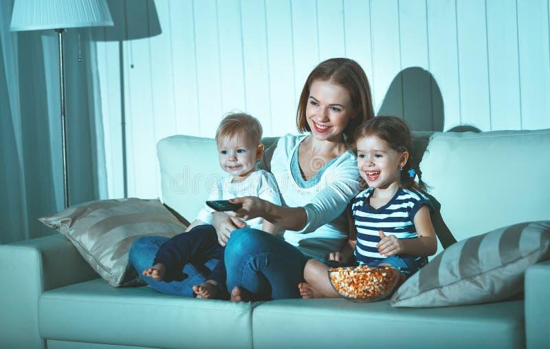 Mãe e crianças da família que olham a televisão em casa fotos de stock