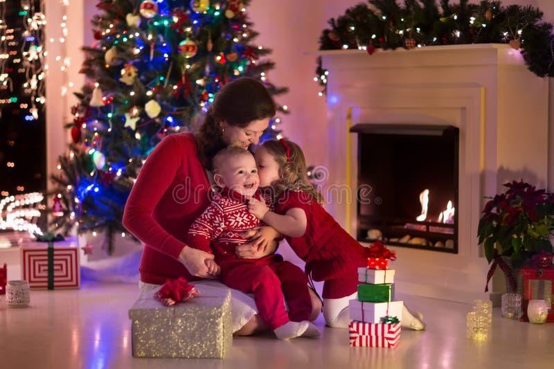 Mãe e crianças em casa na Noite de Natal fotografia de stock royalty free