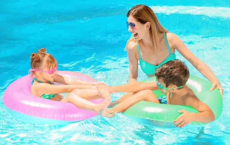 Mãe e crianças felizes com os anéis infláveis que descansam na piscina foto de stock royalty free