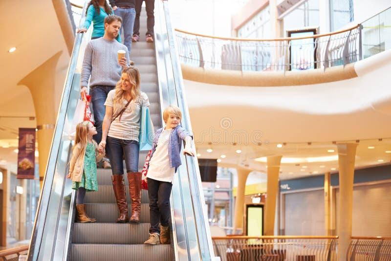 Mãe e crianças na escada rolante no shopping fotografia de stock