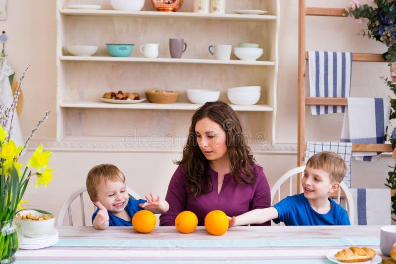 Mãe e crianças na tabela na cozinha Conceito de família feliz imagem de stock