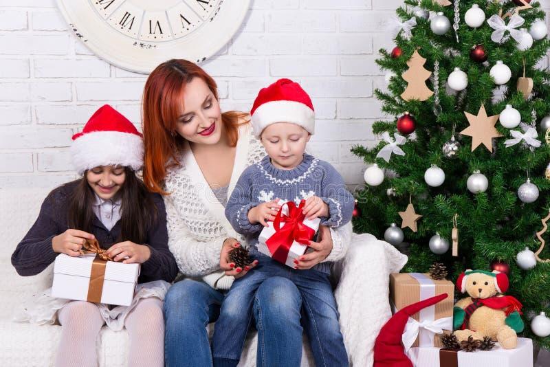 Mãe e crianças novas com as caixas de presente na frente de Christm fotografia de stock royalty free