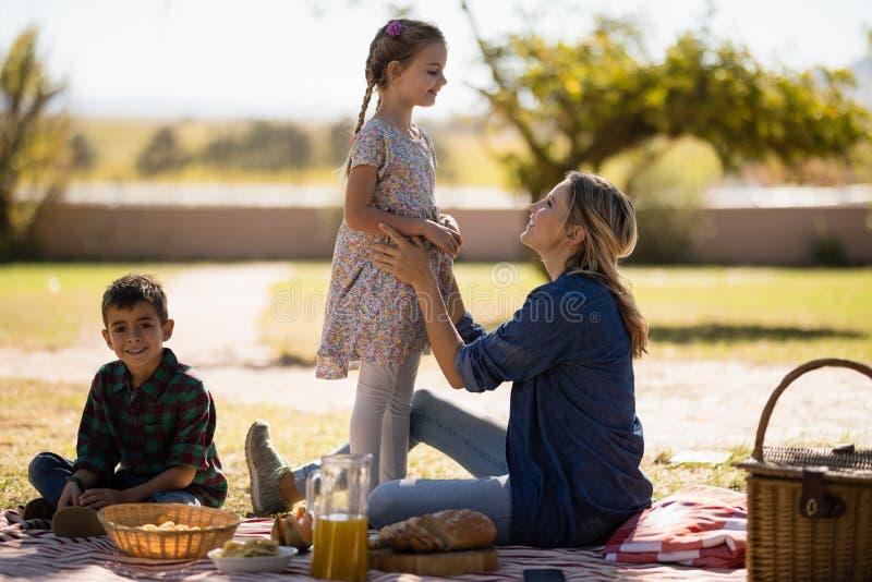 Mãe e crianças que apreciam junto no piquenique no parque fotografia de stock