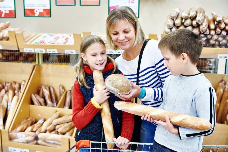 Mãe e crianças que compram o pão imagens de stock