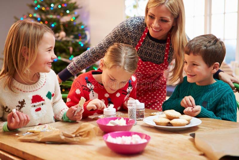 Mãe e crianças que decoram cookies do Natal junto foto de stock royalty free