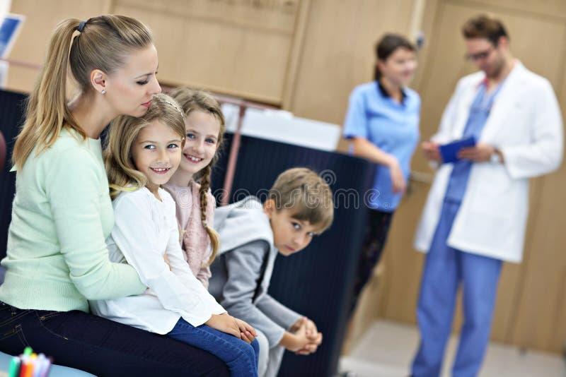 Mãe e crianças que esperam na frente da mesa de registro no hospital foto de stock