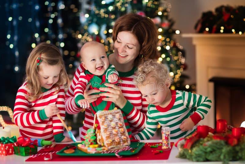 Mãe e crianças que fazem a casa do pão do gengibre no Natal imagem de stock