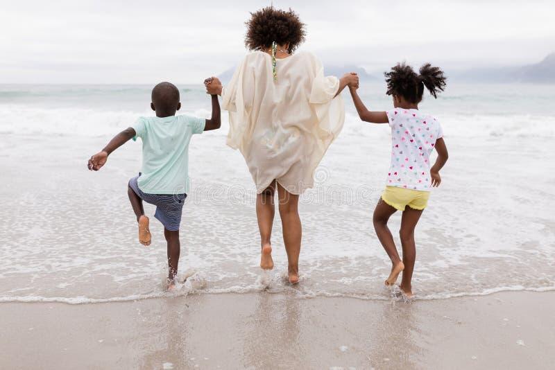 Mãe e crianças que jogam junto na praia imagem de stock
