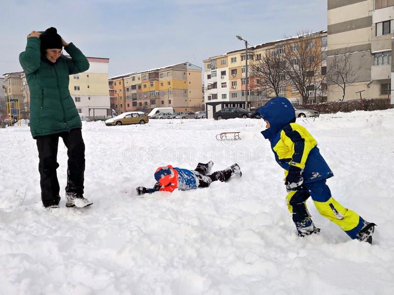 Mãe e crianças que jogam na neve fotografia de stock royalty free