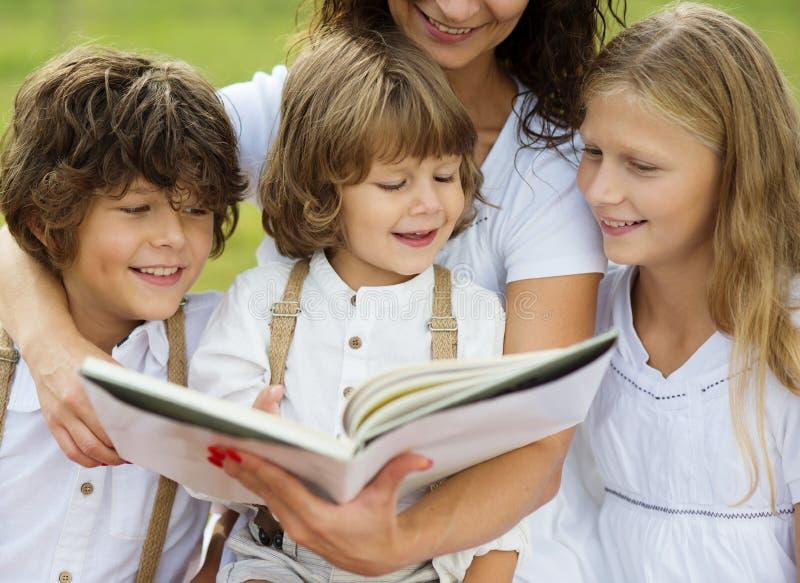 Mãe e crianças que leem um livro foto de stock