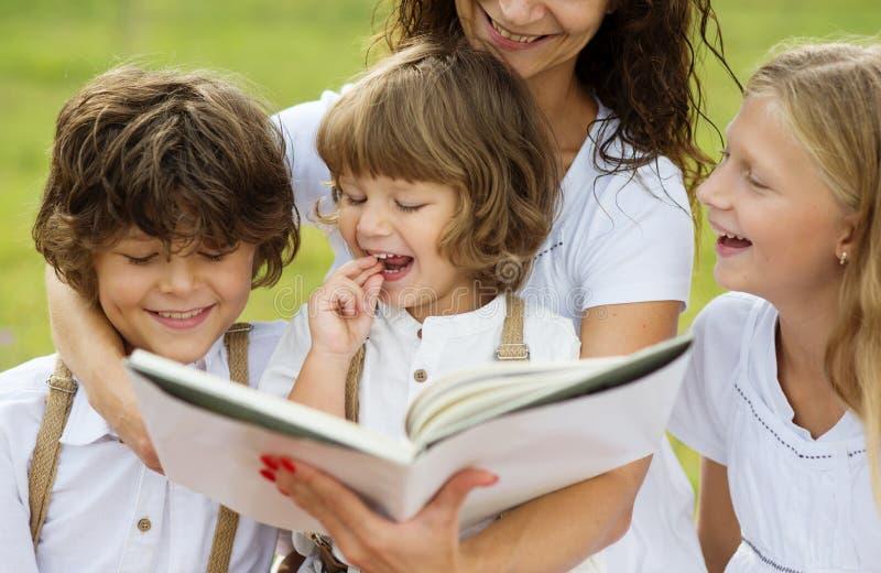 Mãe e crianças que leem um livro fotos de stock
