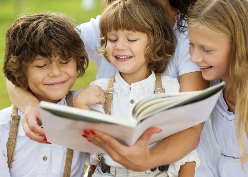 Mãe e crianças que leem um livro fotografia de stock royalty free