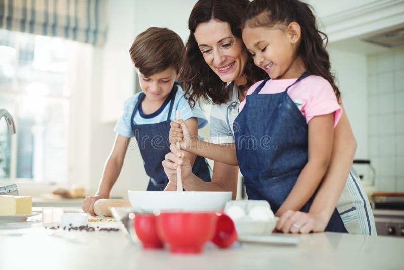 Mãe e crianças que misturam a massa ao preparar cookies fotografia de stock royalty free