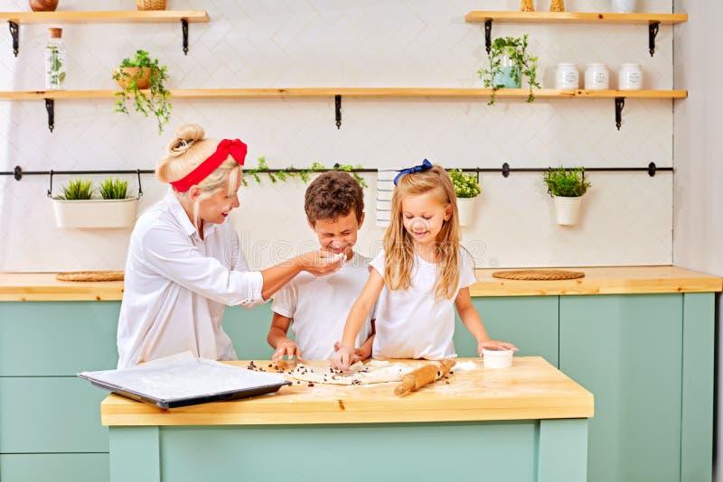 Mãe e crianças que preparam a pastelaria na cozinha imagem de stock