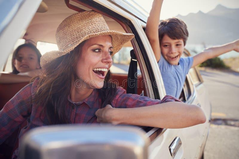 Mãe e crianças que relaxam no carro durante a viagem por estrada imagens de stock